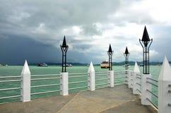 Vue de la jetée de mer vers la mer de turquoise avec des bateaux sur le fond d'un ciel orageux sombre photo libre de droits