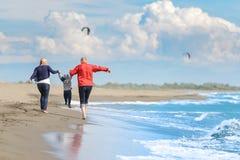 Vue de la jeune famille heureuse ayant l'amusement sur la plage Image libre de droits