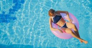 Vue de la jeune natation de femme de brune sur l'anneau rose gonflable photographie stock libre de droits
