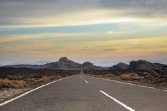 Vue de la longue route au milieu du désert Photos libres de droits