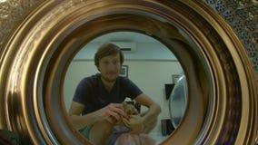 Vue de la machine ? laver comme un jeune homme met les v?tements sales dans elle banque de vidéos