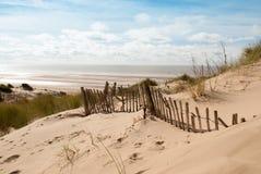 Vue de la mer de la dune de sable avec la vieille barrière Photo stock