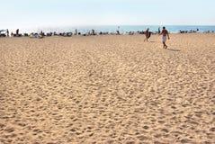 Vue de la plage Touristes, lits pliants et parapluies le jour chaud d'été Images libres de droits
