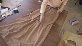 Vue de la robe sur la table que le tailleur féminin emballe pour l'acheteur clips vidéos
