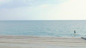 Vue de la terrasse en bois des conseils à la mer et au ciel Deux rameurs nagent sur les conseils du cadre Copiez l'espace clips vidéos
