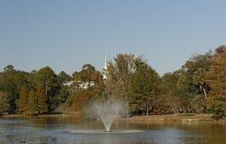 Vue de lac de fontaine et d'église Steeple d'arbres Image stock