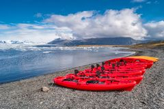 Vue de lagune de glacier avec des icebergs et des canoës rouges dans la rangée, Jokulsarlon, Islande, heure d'été images libres de droits