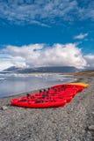Vue de lagune de glacier avec des icebergs et des canoës rouges dans la rangée, Jokulsarlon, Islande, heure d'été photographie stock libre de droits