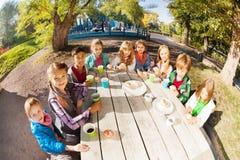 Vue de lentille grande-angulaire des enfants buvant du thé Images stock
