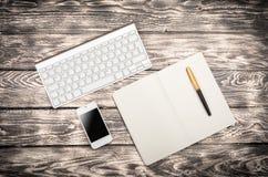 Vue de lieu de travail d'en haut : clavier, livre, téléphone portable Image libre de droits