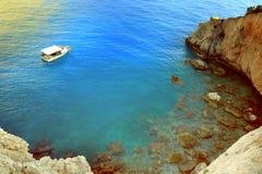 Vue de littoral d'été de la Grèce Eau, montagne et bateau bleus de mer Photographie stock