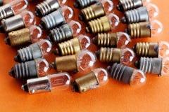 Vue de macro de lampes de vintage Les ampoules avec le bronze et l'argent texturisés d'or apprêtent Fond orange, macro vue Image libre de droits