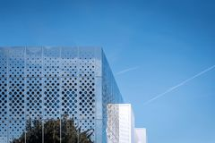 Vue de matin reflétant la surface moderne brillante de bâtiment sur le ciel bleu à l'arrière-plan Photos stock