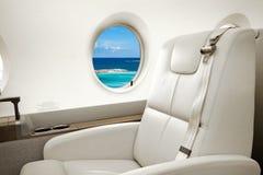 Vue de mer et de plage dans la fenêtre d'avions, vol d'avion d'affaires images stock