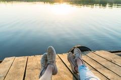Vue de mode de vie des jambes du ` un s de couples utilisant des espadrilles sur un p en bois Photographie stock