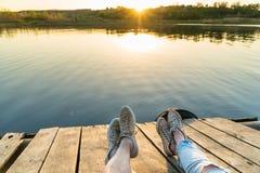 Vue de mode de vie des jambes du ` un s de couples utilisant des espadrilles sur un p en bois Photographie stock libre de droits