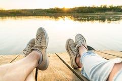 Vue de mode de vie des jambes du ` un s de couples utilisant des espadrilles sur un p en bois Image libre de droits