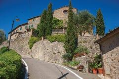 Vue de mur, de vieilles maisons et d'église près de route dans la campagne toscane Image libre de droits
