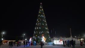 Vue de nuit d'arbre de Noël pendant la bonne année neigeuse de ville Laps de temps banque de vidéos