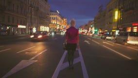 Vue de nuit d'une route et d'un backview de fille s'attaquant au centre de la route clips vidéos
