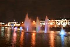 Vue de nuit des belles fontaines de flottement multicolores sur la rivière le long de la rue photographie stock