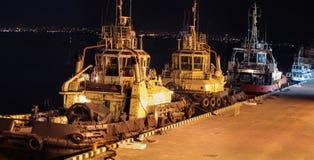 Vue de nuit des trois remorqueurs dans le port de cargaison photo stock
