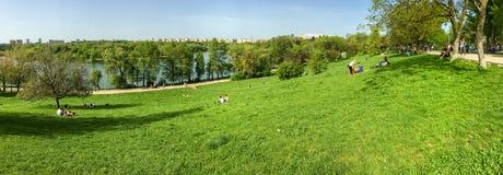 Vue de panorama des personnes détendant et ayant le pique-nique en parc public des jeunesse Photographie stock libre de droits