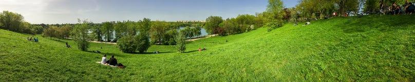 Vue de panorama des personnes détendant et ayant le pique-nique en parc public des jeunesse Photo libre de droits