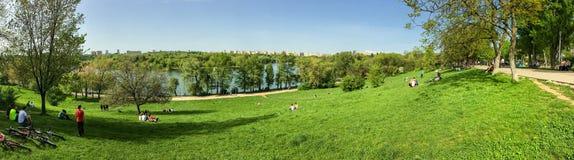 Vue de panorama des personnes détendant et ayant le pique-nique en parc public des jeunesse Images stock