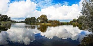 Vue de panorama de la ville Zoeterwoude-dorp avec la réflexion des beaux cieux nuageux dans l'eau Photographie stock libre de droits