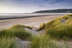 Vue de paysage de soirée d'été au-dessus des dunes de sable herbeuses sur la plage Image stock