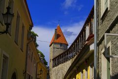 Vue de paysage de fond de la rue tordue de la vieille ville à Tallinn, et le vieux mur de forteresse avec la tour photo stock