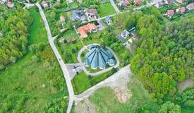 Vue de perspective aérienne sur la ville touristique avec l'église catholique entourée par les prés et la forêt photographie stock