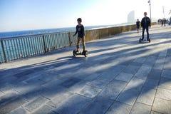 Vue de perspective de bord de mer de Barcelone Espagne de deux enfants conduisant des hoverboards Images stock
