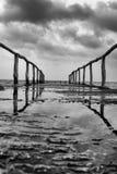 Vue de perspective d'un pilier sur le bord de la mer avec la mer bleue claire et le ciel dramatique Images libres de droits