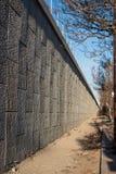 Vue de perspective de la saleté et des débris sur le secteur étroit de passage couvert près du mur d'une route élevée Photos stock