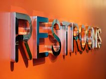 Vue de perspective orange de mur des textes d'argent des toilettes 3d Photographie stock