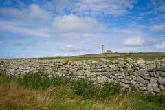 Vue de phare de Lundy avec un mur dans le premier plan Image stock
