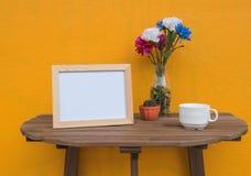 Vue de photo et tasse et fleurs dans le pot sur un en bois sur le fond jaune Photo stock
