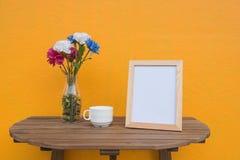 Vue de photo et tasse et fleurs dans le pot sur un en bois sur le fond jaune Images libres de droits