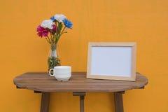Vue de photo et tasse et fleurs dans le pot sur un en bois sur le fond jaune Photographie stock libre de droits