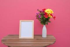 Vue de photo sur un en bois et des fleurs dans le pot sur le fond rose Photos stock