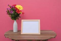 Vue de photo sur un en bois et des fleurs dans le pot sur le fond rose Image stock