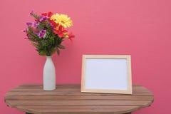 Vue de photo sur un en bois et des fleurs dans le pot sur le fond rose Photo stock
