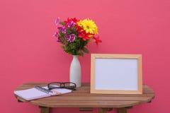 Vue de photo sur une table et un livre et des fleurs en bois dans le pot sur le fond rose Photo libre de droits