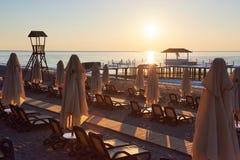 Vue de plage sablonneuse privée avec des lits du soleil et parasokamy scéniques la mer et les montagnes ressource Image stock