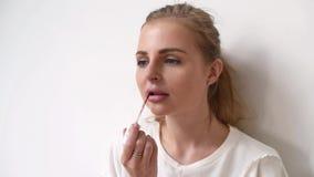 Vue de plan rapproché d'une jeune femme appliquant le rouge à lèvres sur ses lèvres clips vidéos