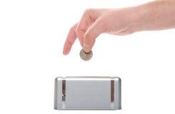 Vue de plan rapproché d'une main, d'une pièce de monnaie et d'un moneybox humains. photo libre de droits