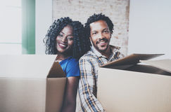 Vue de plan rapproché de jeune homme d'africain noir et de ses boîtes mobiles d'amie dans la nouvelle maison ensemble et faisant  Photos stock