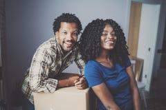 Vue de plan rapproché de jeune homme d'africain noir et de ses boîtes mobiles d'amie dans la nouvelle maison ensemble et faisant  Photos libres de droits